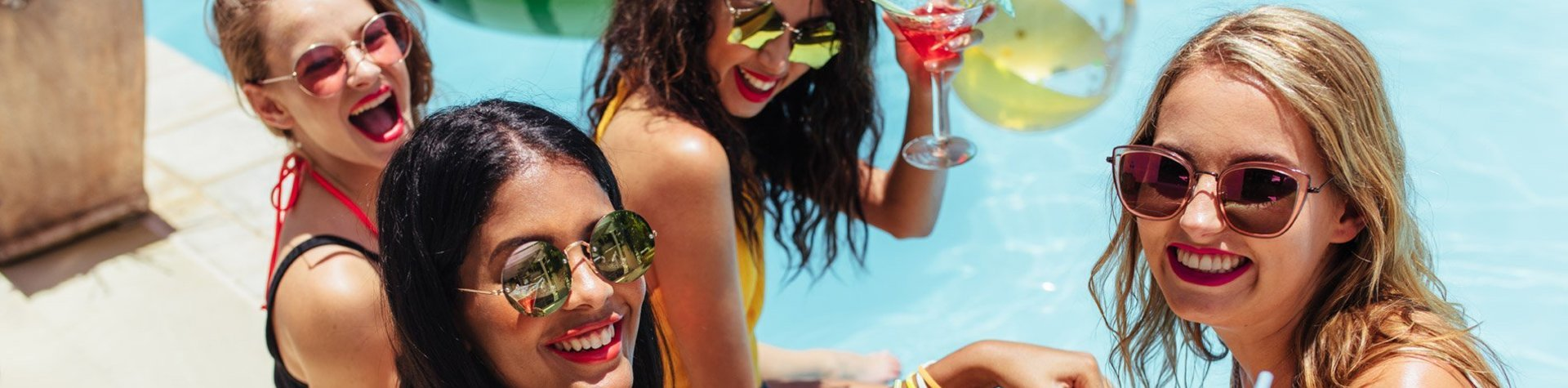 girls drinking cocktails in pool