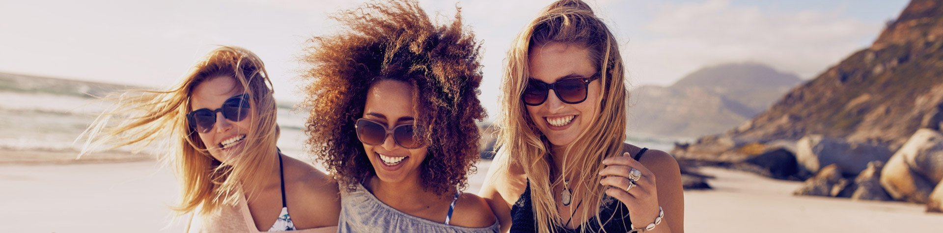three girls walking along beach smiling